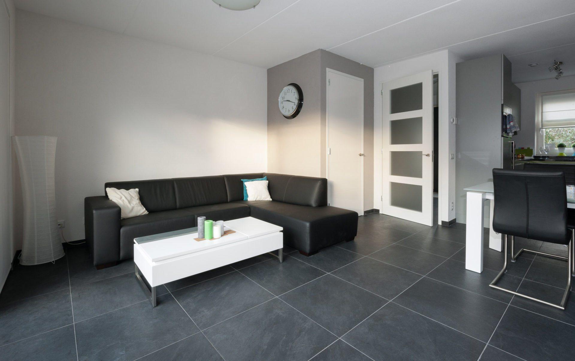 Antraciet vloertegels in woonkamer en badkamer for Grijze woonkamer