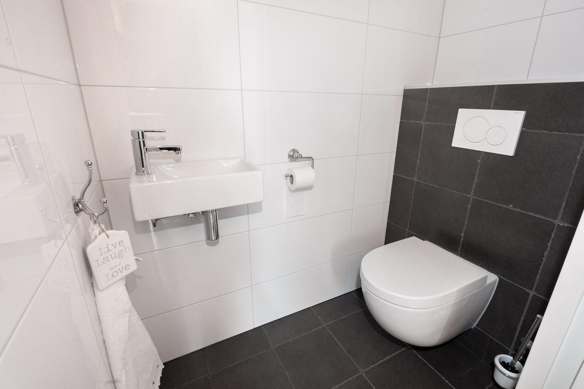 Houtlook tegels in woonkamer, zwart/wit geblokte vloer in hal