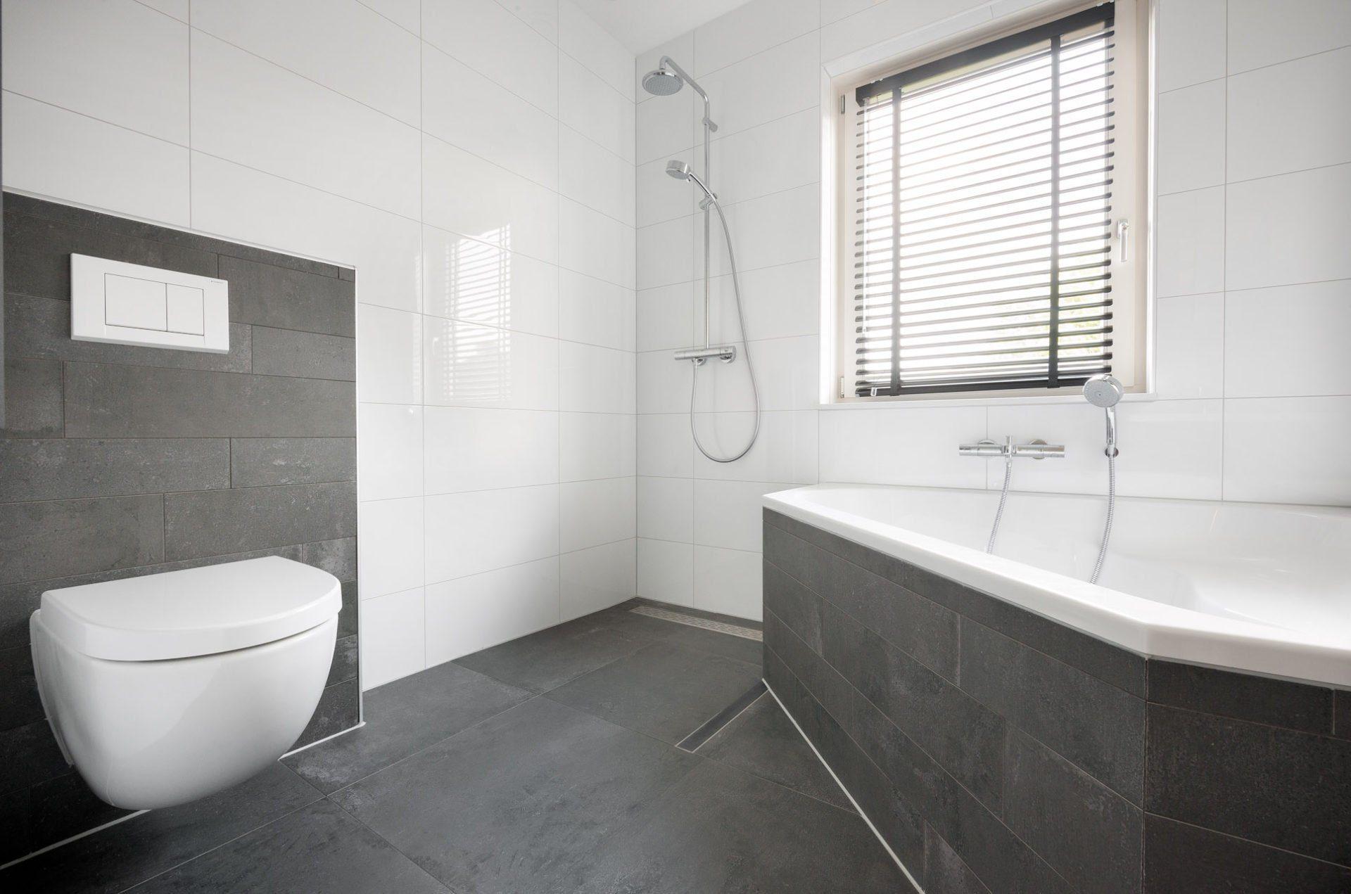 Antraciet vloertegels in woonkamer en badkamer - Marmeren douche ...