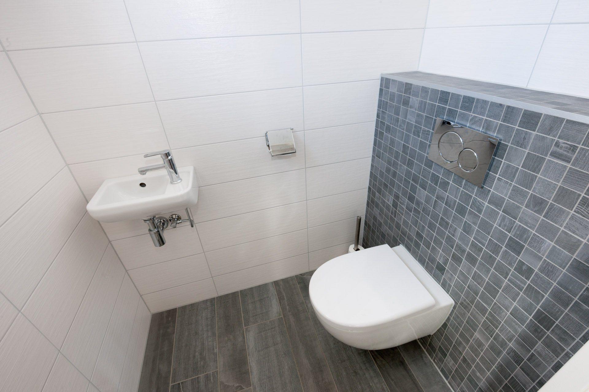 Houtlook tegels in woonkamer en mozaïek in toilet kroon