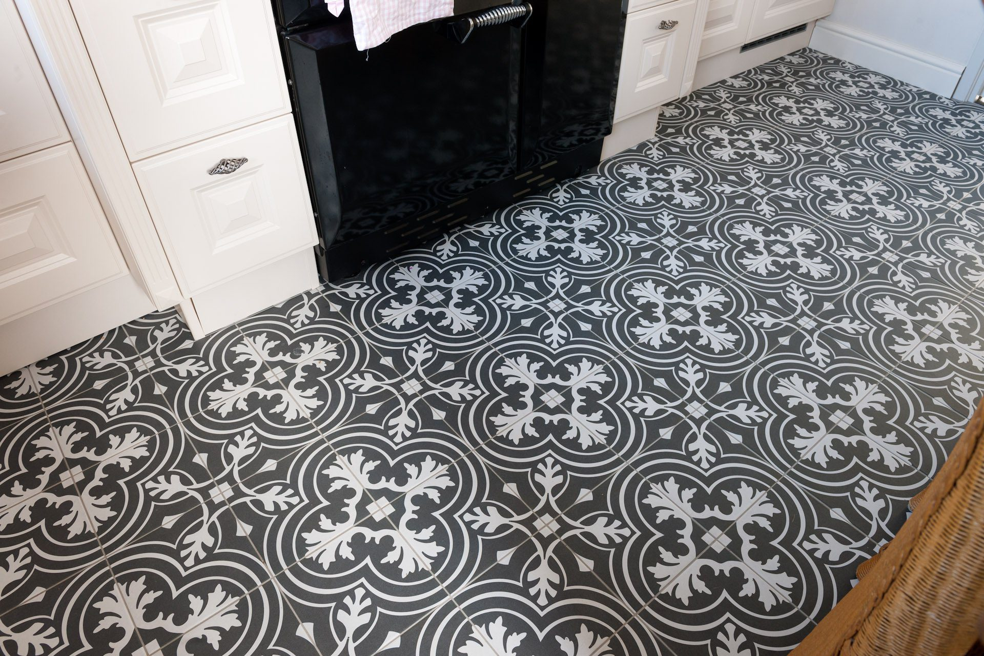 Houtlook vloer in woonkamer, donkere patroontegels in keuken
